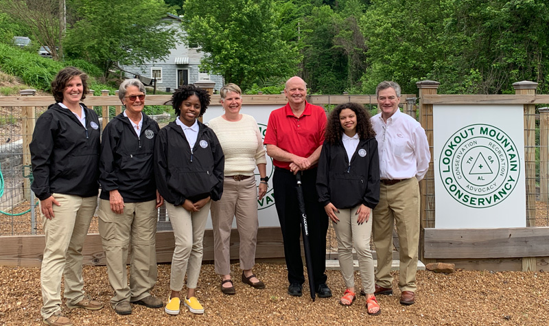 Interns stand with staff from LMC, Ruby Falls, Rock City, and Coca Cola in front of the vegetable garden
