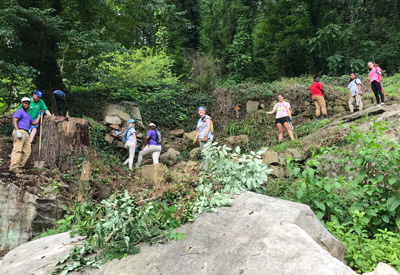 Interns and youth works clearing a wall
